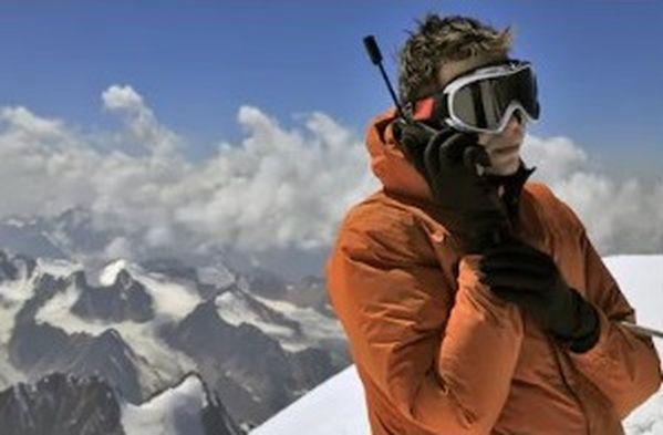 homme utilisant un téléphone satellite en randonnée en haute montagne